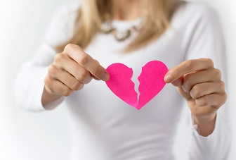 Woman symbolically tearing up pink paper heart