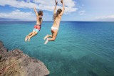 Friends cliff jumping into the ocean, summer fun lifestyle.