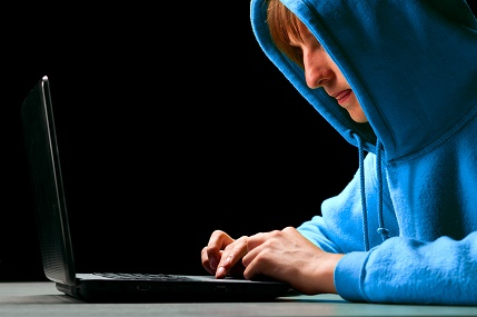 hacker. Young man is typing on laptop and looking at screen
