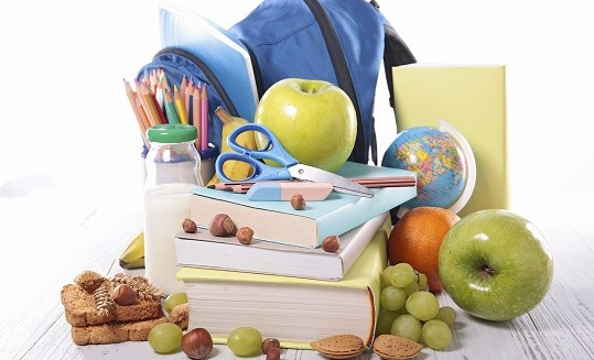 school lunch with fruit and school supplies