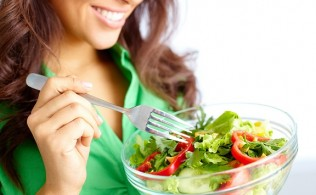 Close-up of pretty girl eating fresh vegetable salad