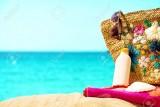 30440355-Suntan-cream-hat-bag-and-sunglasses-by-the-sea-Stock-Photo